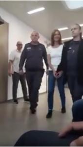 העיתונאית עצירה לורי שם טוב מולכת בבגדי אסיר באזיקים בידיים וברגליים לדיון תביעה אזרחית